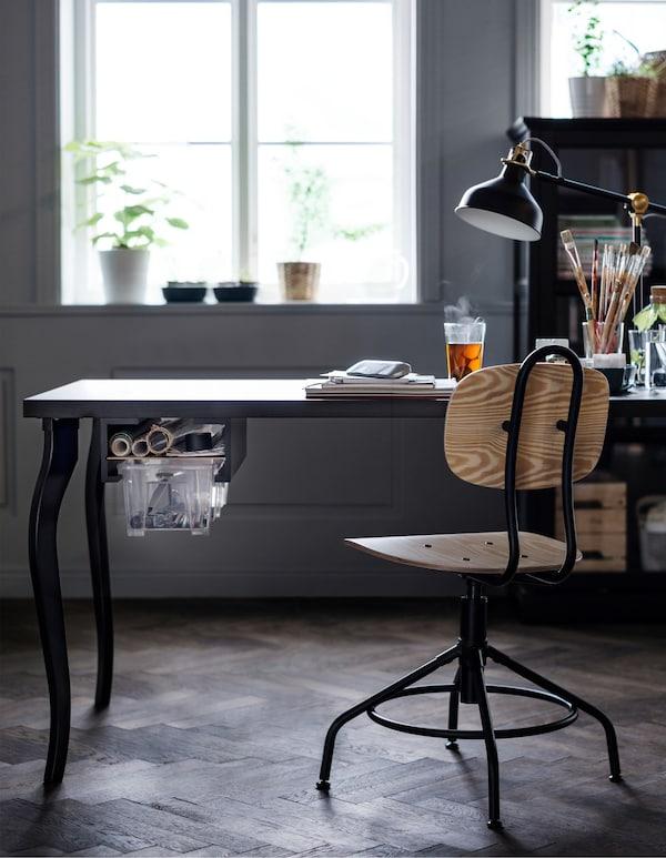 Una mesa negra con un cajón creativo se usa como escritorio para un espacio de oficina en casa.