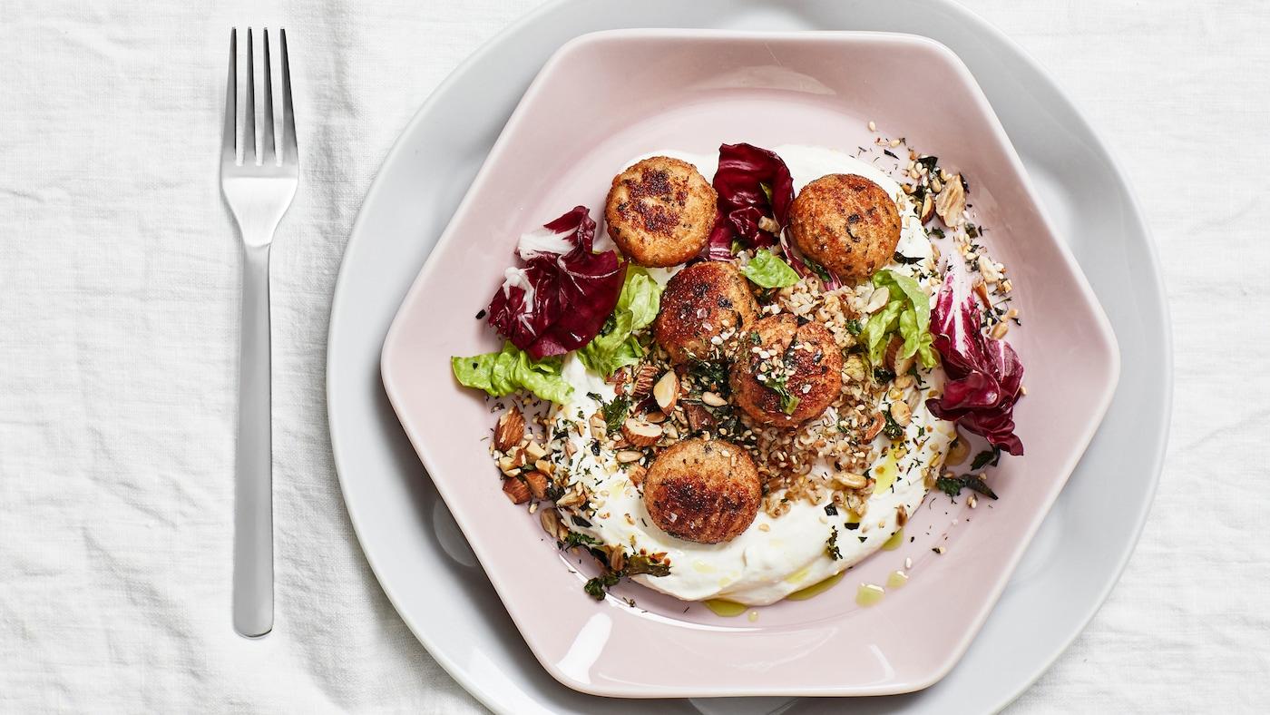 Una mesa preparada con un mantel blanco, un tenedor y un plato con forma de octógono en rosa polvoriento con cinco albóndigas de bacalao, verduras, frutos secos y yogur.