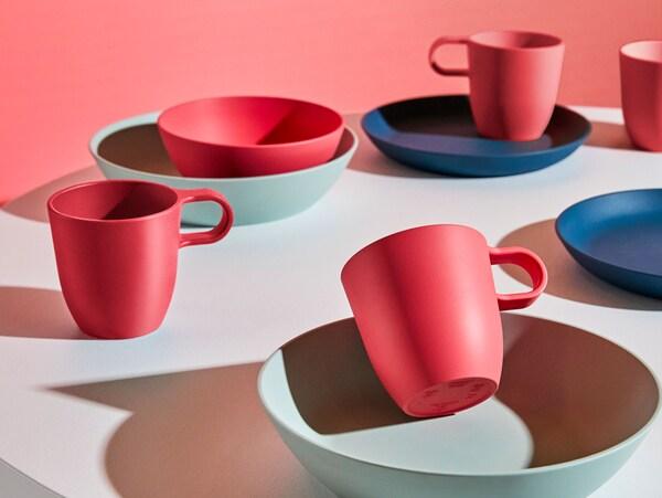 Una mesa redonda con pratos vermellos, azuis escuros e verdes pálidos, cuncas da serie IKEA TALRIK de plástico PLA.