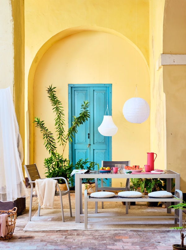 Una mesa, un banco y sillas sobre una alfombra, y farolillos blancos. De fondo se ven una puerta azul y una pared amarilla.