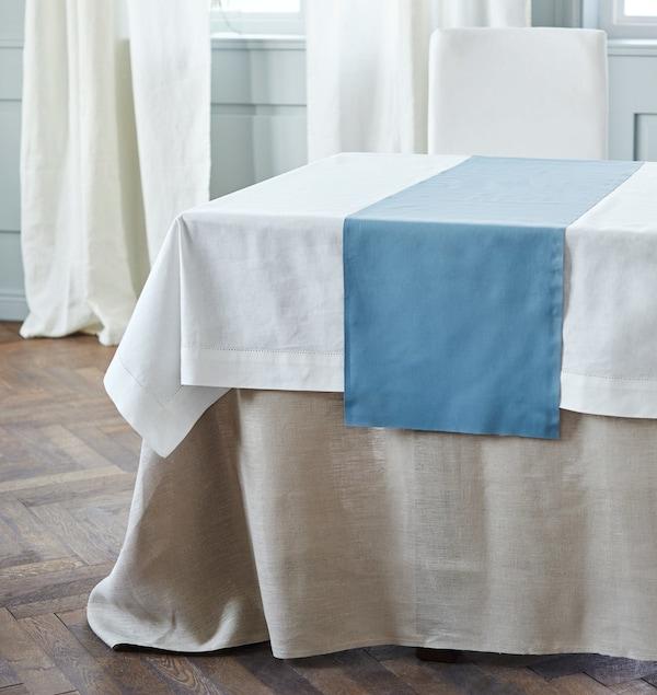 Una mesa vestida con tres capas de tejidos de diferentes largos.