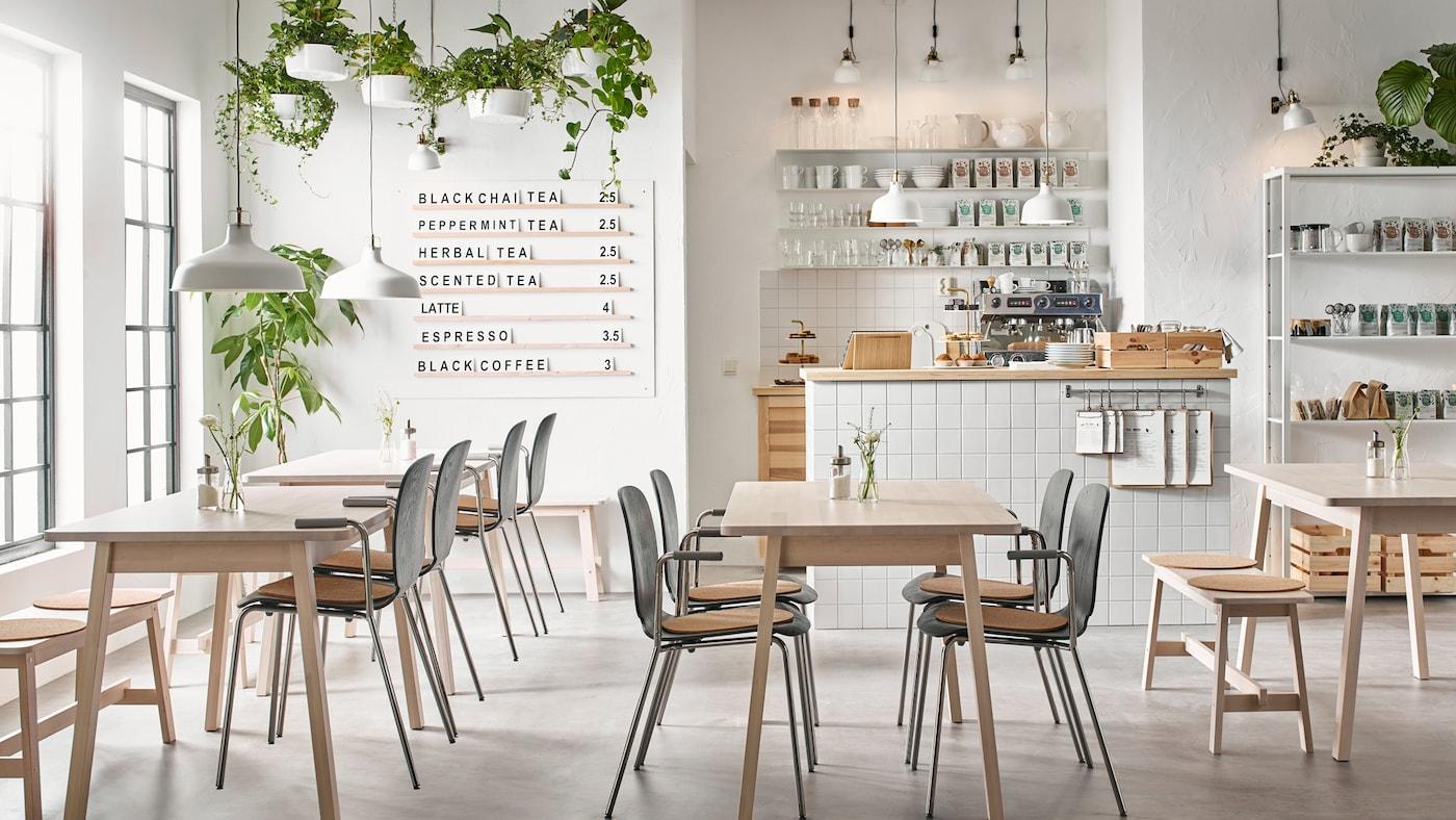 Una moderna cafetería de color beige, blanco y negro con mesas NORRÅKER de abedul blanco y sillas en negro y cromo.
