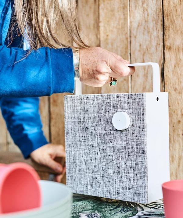 Una mujer coloca un altavoz blanco con mango en una mesa cubierta de tela por una pared con paneles de madera.