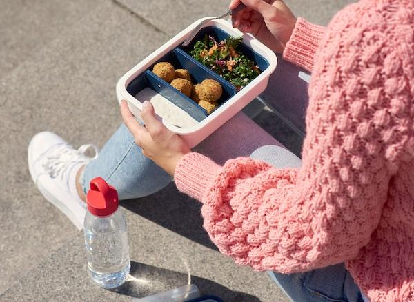 Una mujer comiendo de un recipiente de plástico para alimentos de IKEA con una botella de plástico transparente llena de agua a su lado.