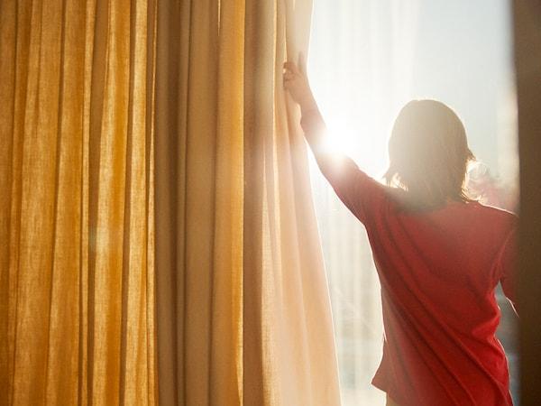 Una mujer joven con una camiseta roja abriendo una cortina amarilla para saludar al sol desde el balcón.