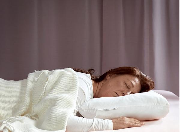 Una mujer joven duerme plácidamente boca abajo con una almohada ergonómica IKEA SKOGSLÖK.