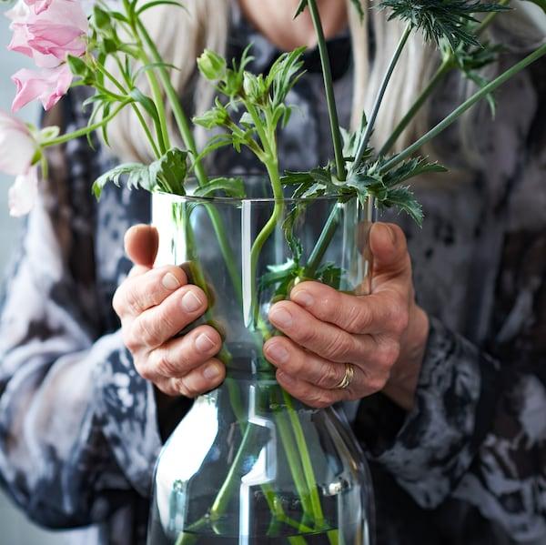 Una mujer mayor sujeta un jarrón OMTÄNKSAM con tallos minuciosamente dispuestos. La forma del jarrón hace que sea fácil de levantar y transportar.