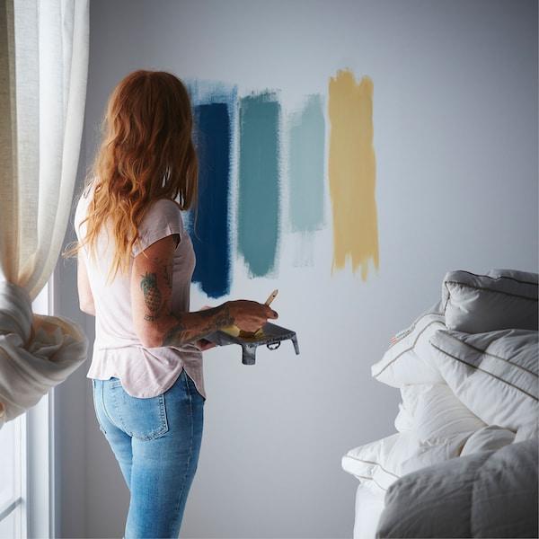 Una mujer prueba varios colores de pintura para su dormitorio pintándolos como muestra en la pared.