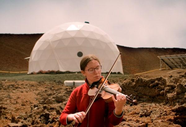 Una mujer tocando el violín delante de una estructura arquitectónica blanca en un paisaje árido.