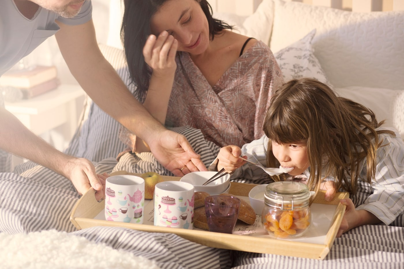 Una mujer y su hija tomando desayuno en la cama, con una bandeja. Comen cosas con cucharas y hay dos tazas.