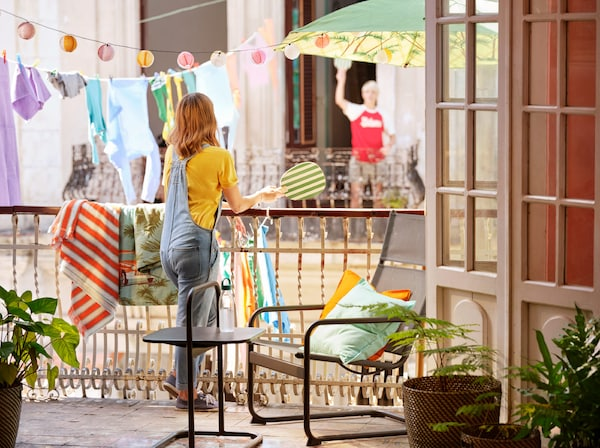 Una nena amb una raqueta de platja està recolzada a la barana d'un balcó, amb llums i peces de roba penjades al fons.