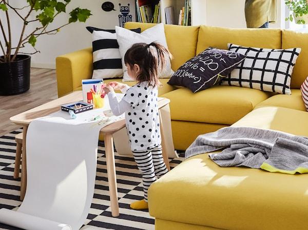 Una niña dibujando en un largo rollo de papel sobre una mesa de café junto a un sofá modular de tres plazas IKEA VIMLE de color amarillo.