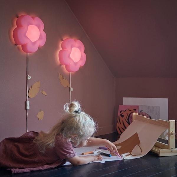 Una niña está pintando en el suelo y dos lámparas de pared en forma de flores iluminan la zona de juego, de IKEA.