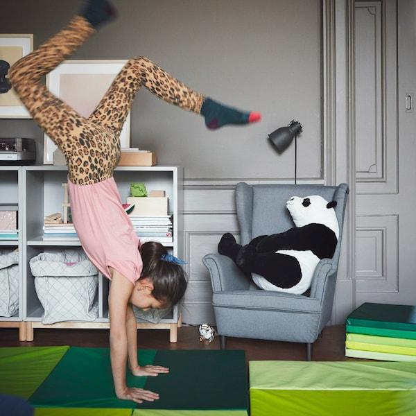 Una niña haciendo el pino en una alfombra de gimnasio plegable IKEA PLUFSIG de color verde.