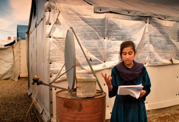 Una niña leyendo un libro delante de una antena parabólica improvisada y refugios provisionales.