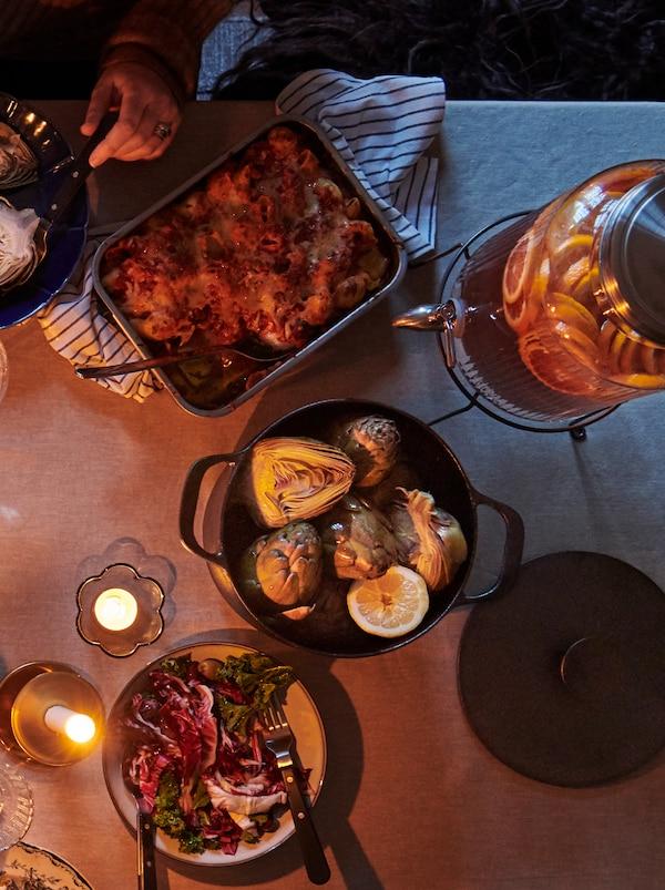 Una olla de hierro fundido con una tapa a su lado y una bandeja para horno llena de comida deliciosa. Las velitas crean un ambiente acogedor.