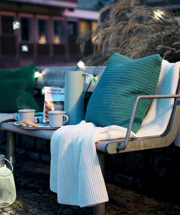 Una panchina in città, di sera, con un vassoio per il caffè, cuscini, un plaid, delle luci decorative e una lanterna SOLVINDEN - IKEA