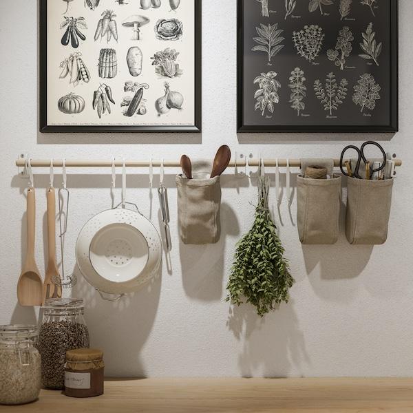 Una pared blanca con dos marcos KNOPPÄNG con pósteres y rieles de abedul NEREBY con utensilios de cocina y recipientes colgados.