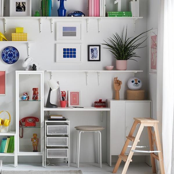 Una pared blanca con estanterías blancas con libros y objetos de distintos colores, una zona de escritorio y un taburete redondo debajo.