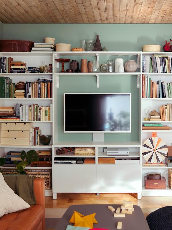 Una pared de almacenamiento de sala de estar con todo incluido formada por una combinación que incluye estanterías BILLY blancas y un mueble para TV BESTÅ.