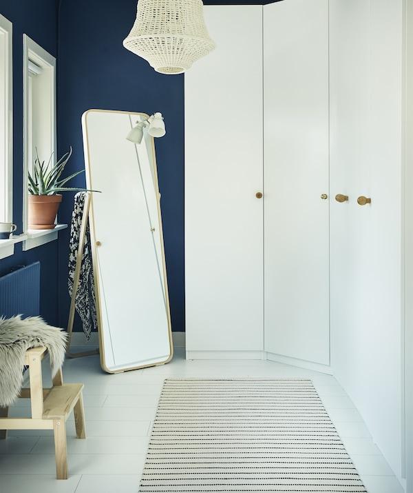 Una pared de armarios blancos y un espejo en una habitación azul oscuro.