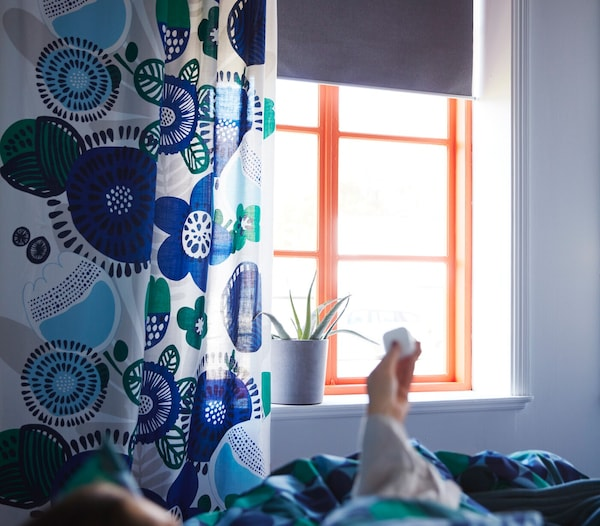Una persona apre una tenda Smart FYRTUR dal letto azionandola con un telecomando - IKEA