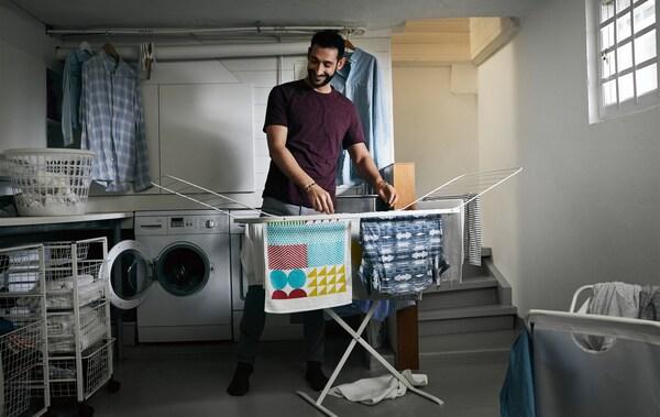 Una persona tiende la ropa en una secadora de aire dentro de una lavandería.