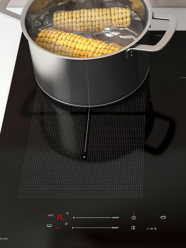 Una placa de inducción con la función de cocción automática; sobre ella hay una olla de acero inoxidable en la que se están hirviendo dos mazorcas de maíz.