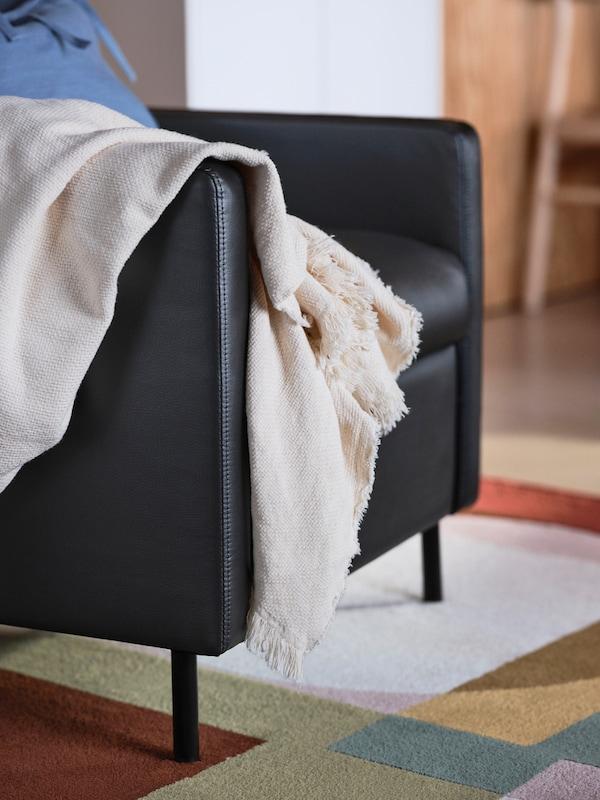 Una poltrona reclinabile GISTAD nera, su un vivace tappeto colorato, con un plaid beige appoggiato sul lato di un bracciolo - IKEA