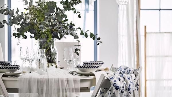 Una romántica mesa redonda puesta, cubierta con un tul blanco y decorada con un jarrón con flores silvestres y hojas de eucalipto.
