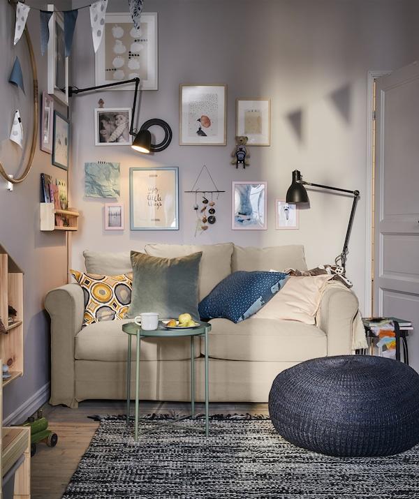 Una sala amb un sofà de dues places, un puf blau fosc i un taula/safata petita de color verd, amb llums negres als dos costats.