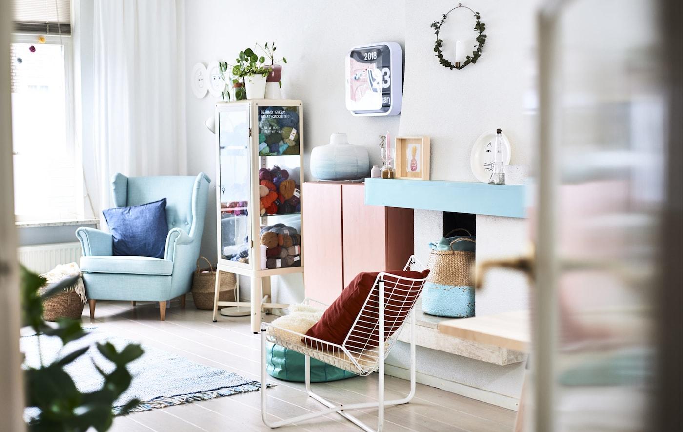 Una sala de estar con muebles y accesorios de colores pastel.