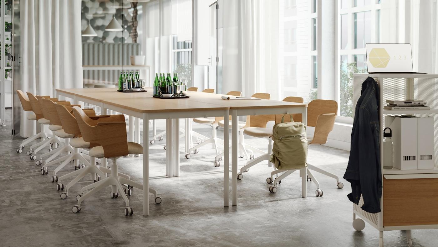 Una sala de reuniones luminosa con mesas y sillas en madera clara y tonos blancos, cortinas blancas traslúcidas y una pared de cristal.