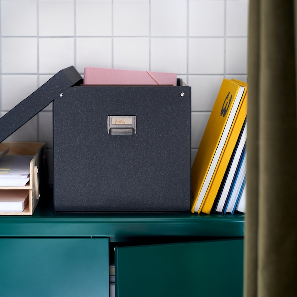 Una scatola portaoggetti TJOG grigio scuro con coperchio si trova sopra un armadietto verde scuro con il coperchio aperto che mostra file rosa.