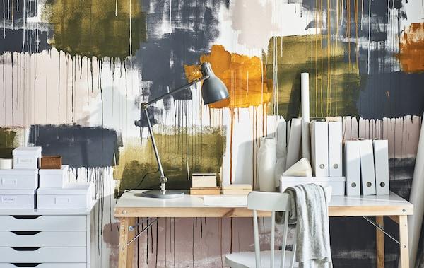 Una scrivania, una cassettiera e una sedia contro la parete di uno studio decorata con schizzi di vernice colorata - IKEA
