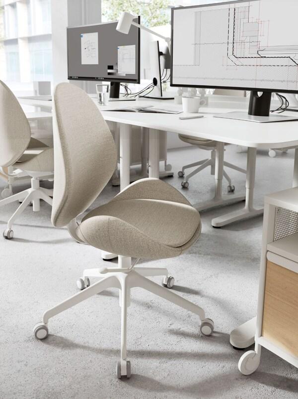 Una sedia da ufficio HATTEFJÄLL in tessuto beige davanti a una scrivania bianca con computer – IKEA