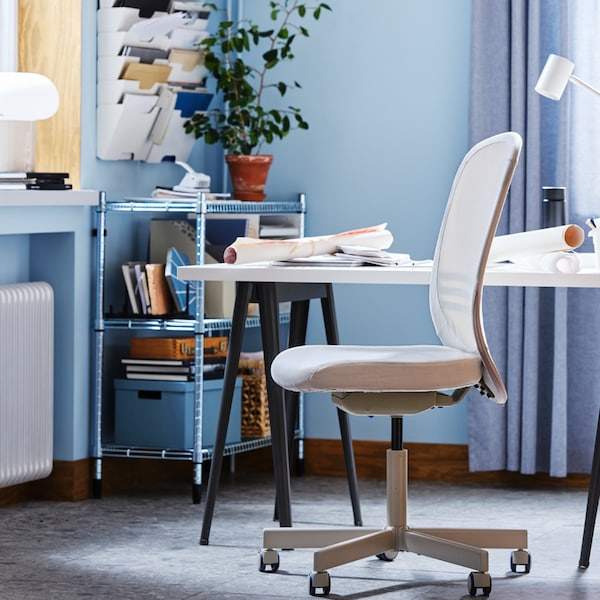 Una sedia girevole FLINTAN accanto a una scrivania bianca e uno scaffale OMAR pieno di carte e scatole di documenti in un ufficio blu.