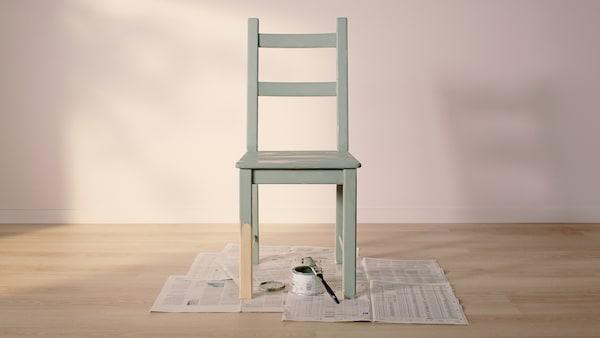 Una sedia in pino IVAR quasi del tutto verniciata di verde, a parte metà di una gamba, sopra dei giornali a terra; accanto un barattolo di vernice e un pennello.