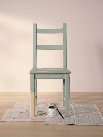 Una sedia IVAR verniciata in verde chiaro posizionata su dei vecchi giornali stesi sul pavimento in legno chiaro di una stanza vuota dalle pareti rosa chiaro.