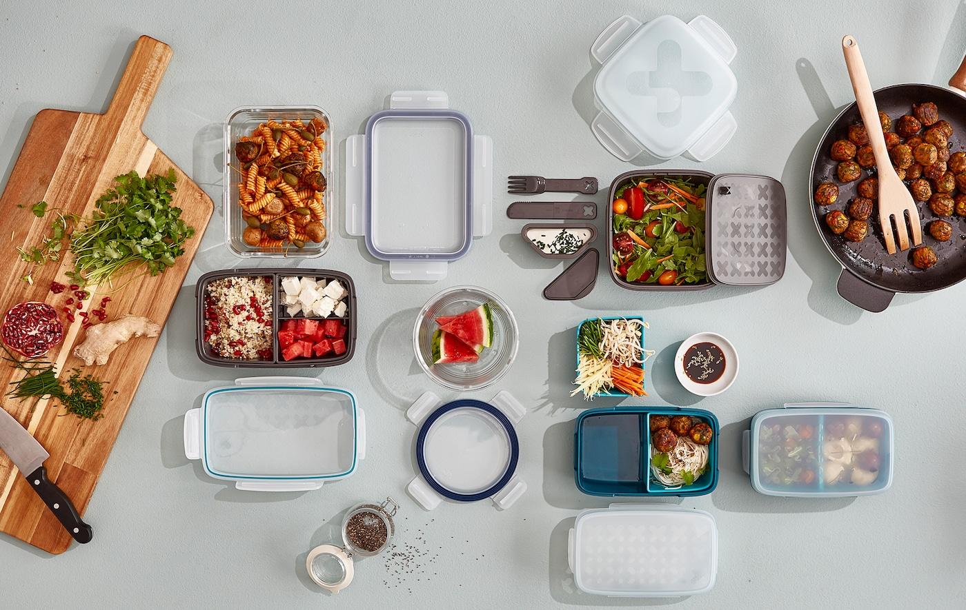 Una selección de recipientes para comida llenándose con alimentos junto a una sartén y una tabla de cortar.