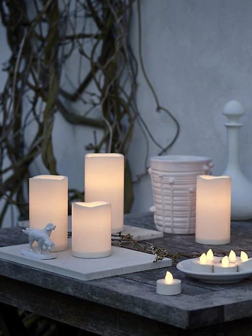 Una selección de velas LED juntas fuera en una mesa de madera frente a una pared blanca.