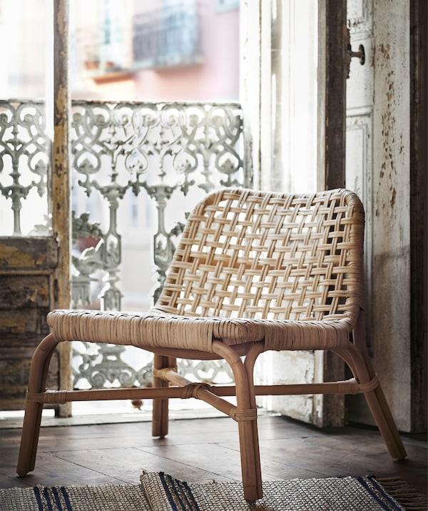 Una silla de ratán TÄNKVÄRD frente a la puerta de un balcón rústico.
