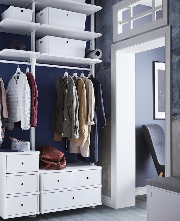 Una solución de almacenaje abierto ELVARLI en un recibidor. La ropa cuelga de un raíl detrás de los estantes con cubos de almacenaje.
