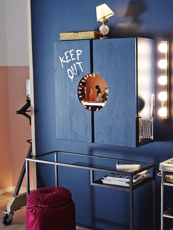 Una stanza blu con una postazione per toeletta ricreata in un mobile dipinto di blu, un tavolo per PC portatile VITTSJÖ e un pouf rosso scuro - IKEA