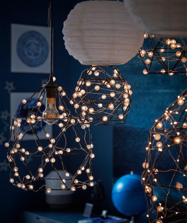Una stanza blu scuro illuminata dalla luna con decorazioni creative ispirate all'astronomia, come il paralume BRUNSTA avvolto dai fili di luci a LED SNÖYRA - IKEA