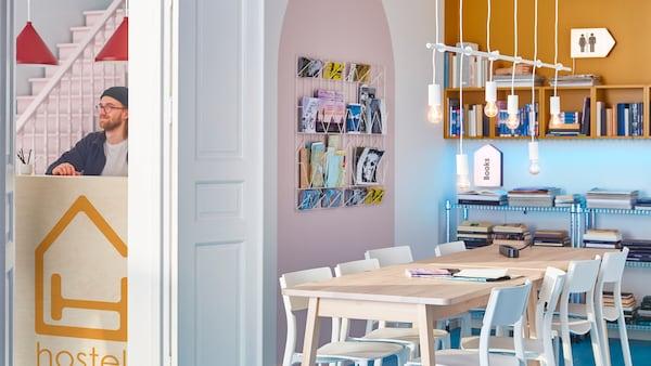Una stanza con un grande tavolo di legno e sedie bianche al centro; attorno soluzioni da parete con giornali e libri - IKEA
