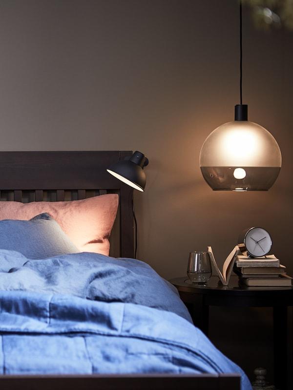 Una struttura letto IDANÄS con copripiumino e federe PUDERVIVA blu scuro accanto a un comodino con sopra una lampada a sospensione - IKEA