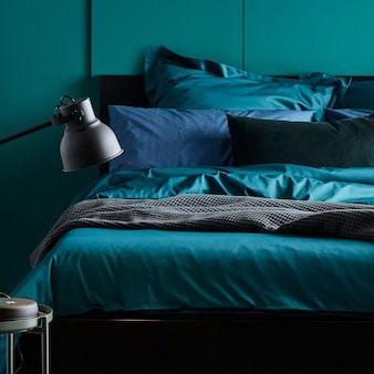 Una struttura letto MALM con biancheria da letto, tra cui copripiumio e federe LUKTJASMIN verde scuro, contro una parete verde in una camera da letto - IKEA