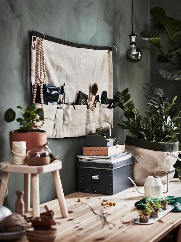 Una taula de fusta enorme amb testos, plantes i un munt d'eines i accessoris de jardineria.