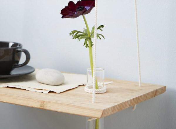 Una tauleta de nit penjant fabricada amb un taula de tallar, amb una copa i una flor en un gerro de vidre.